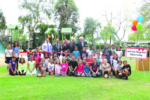 La Mirada Mayor Pauline Deal (center-back) is joined by her City Council counterparts and local children as they unveil the new Neff Park playground.