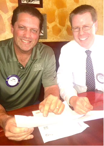 """ROTARY LEADERS PLAN ACTIVITIES -- John Lewis, Rotary President Elect, and current President Russell Hall are pictured planning a busy year of service projects in La Mirada. The major community service project planned by Rotary will be the """"Eileen Wade Clothes for Kids"""" shopping event in December.  The annual project is held in memory of long-time Rotarian Eileen Wade, more than 40 children from La Mirada will be taken to Marshall's department store on Imperial Highway to shop for warm clothing, jackets, and shoes."""