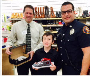 HOLIDAY SPIRIT – Rotary Club of La Mirada President John Lewis (l) and Los Angeles County Fire Department Captain Hugo Valdivia from Fire Station 15 assist a local child select new shoes during the Rotary Club of La Mirada's annual Holiday Shopping Spree at Marshalls.