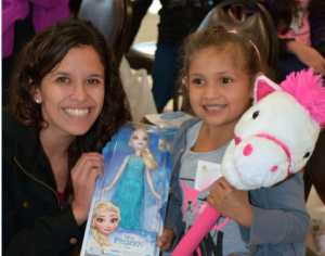 HOLIDAY SMILES -- Volunteer Abby Bracey assists a child at a Christmas party during La Mirada Rotary's Holiday Shopping event.