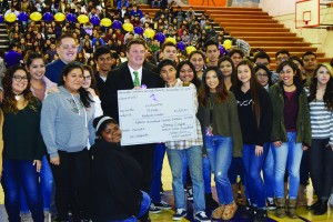 Brian Helleland, executive vice president and chief operation officer of St. Jude Medical Center in Fullerton, accepts a check for $1,520.17 from Norwalk High School students during the school's Charity for Charities fundraiser on Dec. 15.