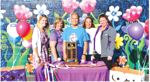 American Cancer Society representatives presented Johnston Elementary School first-grade teacher Dan Calma, center, with a Spirit of Relay award Sept. 23 at the school's flag ceremony. Photo by Tammye Mcduff.