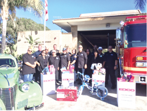 Members of Duke's Car Club with fire station 49 crew with donated toys. These toys will be distributed to children in the local community who might otherwise not have a merry Christmas. The group worked with Pastor Jack Miranda of the Living Faith Church in La Mirada.
